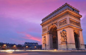 Close up of Arc de Triomphe in Paris, France during sun set