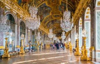 Veranda with multiple chandeliers and gold statues at the Palace of Versailles in France
