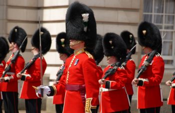 Guards in London wearing tall hats covered in black fur and red suits