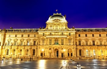 Louvre Museum at night with lights on in Paris, France