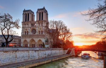 Close up of Notre Dame at sun set next to river in Paris, France