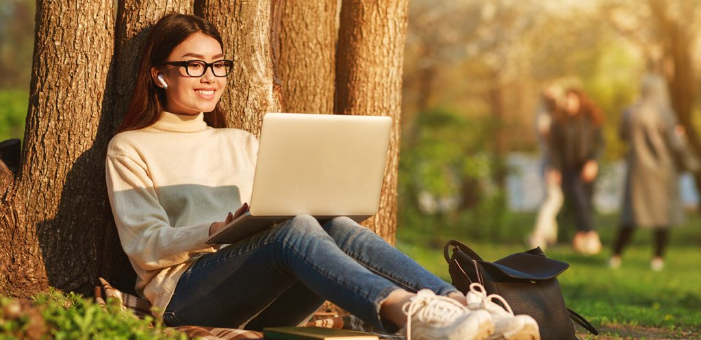 Student with laptop sitting under a tree studying