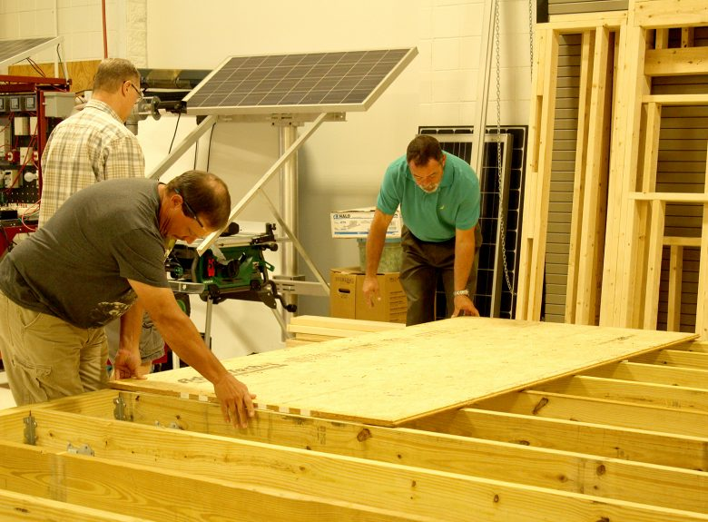 Dennis Baucom instructs students in construction
